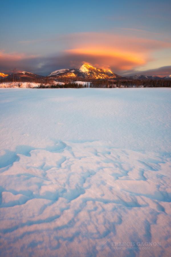 Le soleil levant éclairant les montagnes du Bouclier Canadien (et ce qui semble être des nuages lenticulaires).